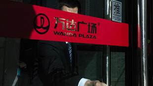 This file photo taken on January 12, 2016 shows a man pushing the door at the entrance of the Chinese conglomerate Wanda Group building in Beijing.