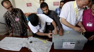 Membros do comitê eleitoral líbio abrem caixa de votos que chegaram de Kufra, no último dia 12 de julho.
