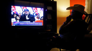 Un hombre observa a al presidente Daniel Ortega hablar por televisiób el 21 de febrero de 2019 en Managua.