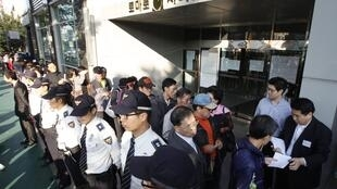 En Corée du Sud, des épargnants font la queue devant le siège social de la caisse d'épargne Tomato de Seongnam, pour obtenir un ticket leur permettant de connaître la date de remboursement de leur épargne, le 22 septembre 2011.