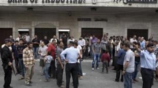 Les forces de sécurité du Hamas montent la garde devant une banque fermée alors que des fonctionnaires de l'Autorité palestinienne venaient retirer leur salaire, le 5 juin 2014.