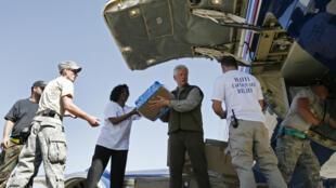L'ex-président américain, Bill Clinton (c), aide à décharger les vivres d'un avion, à l'aéroport de Port-au-Prince, le 18 janvier 2010.