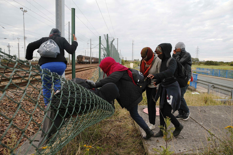 Migrantes tentam acessar o Eurotúnel através de uma brecha em uma barreira em em Frethun, perto de Calais, no norte da França, nesta quinta-feira (29).