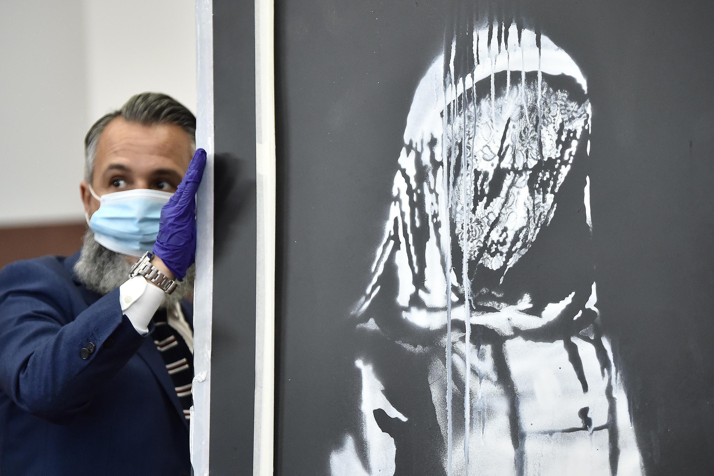La obra de arte atribuida a Banksy pintada en una puerta de emergencia de la sala de conciertos Bataclan de París en 2019, es presentada ante la prensa el 11 de junio de 2020 en L'Aquila, Italia, tras haber sido recuperada de manos de sus ladrones