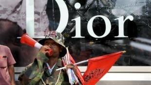 Un contestataire au gouvernement thaïlandais devant la devanture d'un magasin de haute-couture fermé.