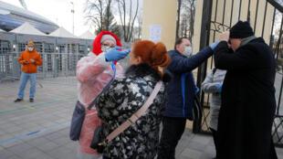 Проверка температуры болельщиков перед матчем «Динамо» Минск — «Торпедо-БелАЗ» в белорусской столице 3 апреля 2020 г.