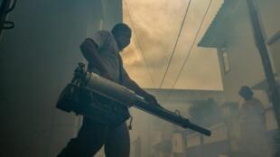 Un homme fumige une zone dans le cadre des mesures communautaires de lutte contre une épidémie de dengue à Jakarta, le 11 avril 2020.