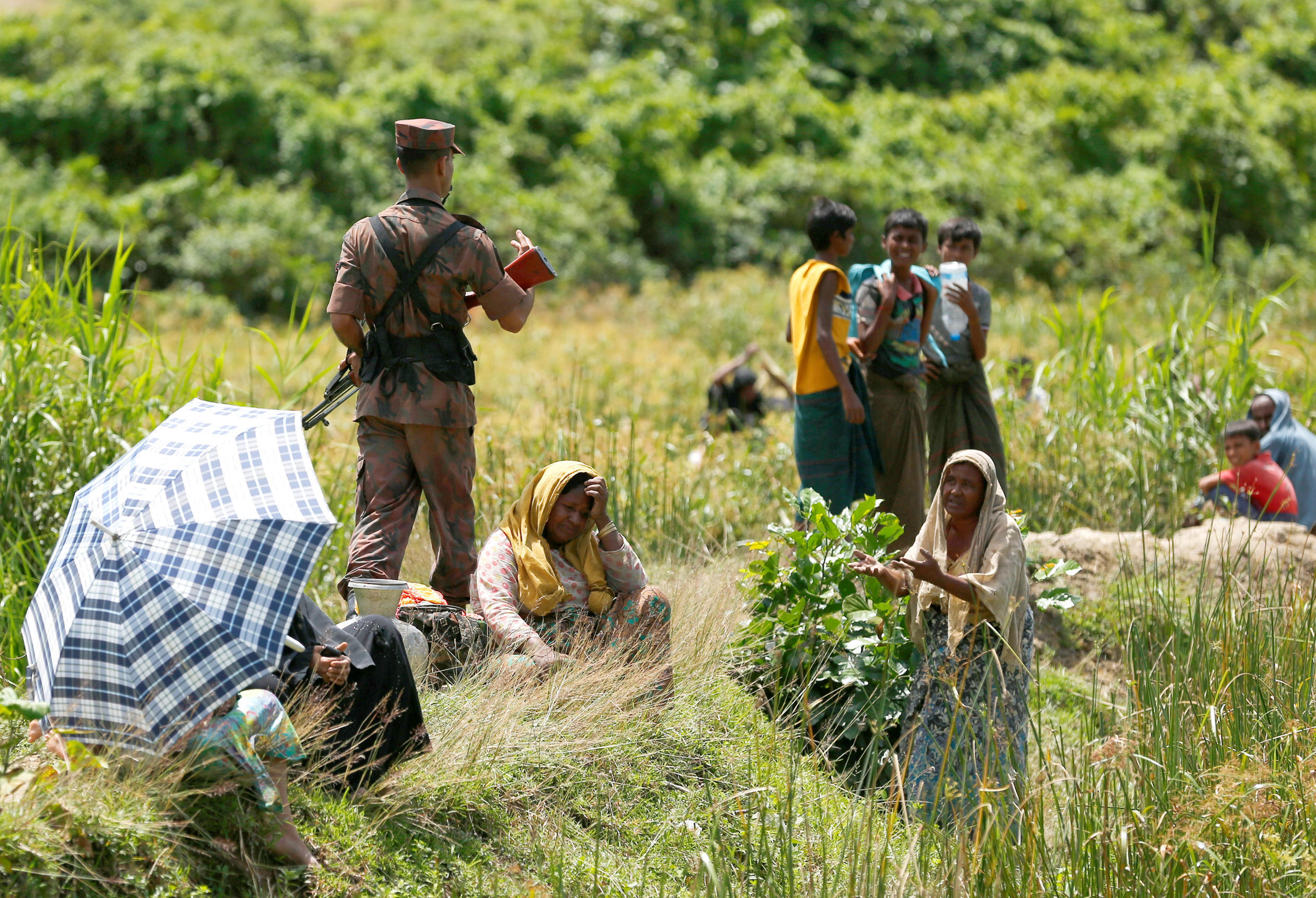 A Rohingya woman urges the member of Border Guard Bangladesh not to turn them back to Myanmar, in Cox's Bazar, Bangladesh, 27 August 2017.