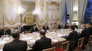 French President Francois Hollande sits facing French Prime Minister Manuel Valls as he presides over an emergency meeting at the Elysee Palace in Paris.