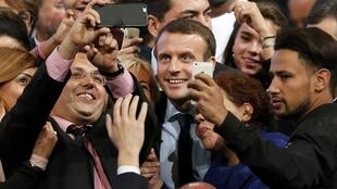 Former French economy minister Emmanuel Macron takes selfies with supporters at the end of his rally for his political movement, En Marche !, or Forward !, in Montpellier, France, October 18, 2016.