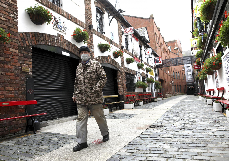 Un homme portant un masque passe devant un pub fermé à Belfast, en Irlande du Nord, le vendredi 16 octobre 2020.
