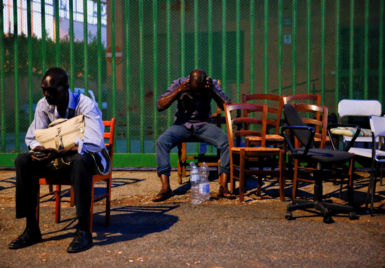 Dos migrantes permanecen en una calle de Roma despues de haber sido desalojados de un edificio. Italia, 9 de julio de 2018.