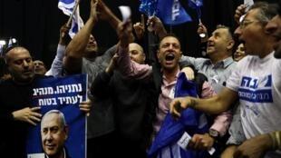 Des militants du Likoud, le parti de Benyamin Netanyahu, se réjouissent suite à la diffusion des premiers sondages à la sortie des urnes, le 2 mars après les élections législatives à Tel Aviv.