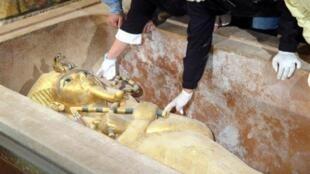 Une équipe d'archéologues égyptiens ouvre  à Louxor le sarcophage en or de Toutankhamon pour le scanner.