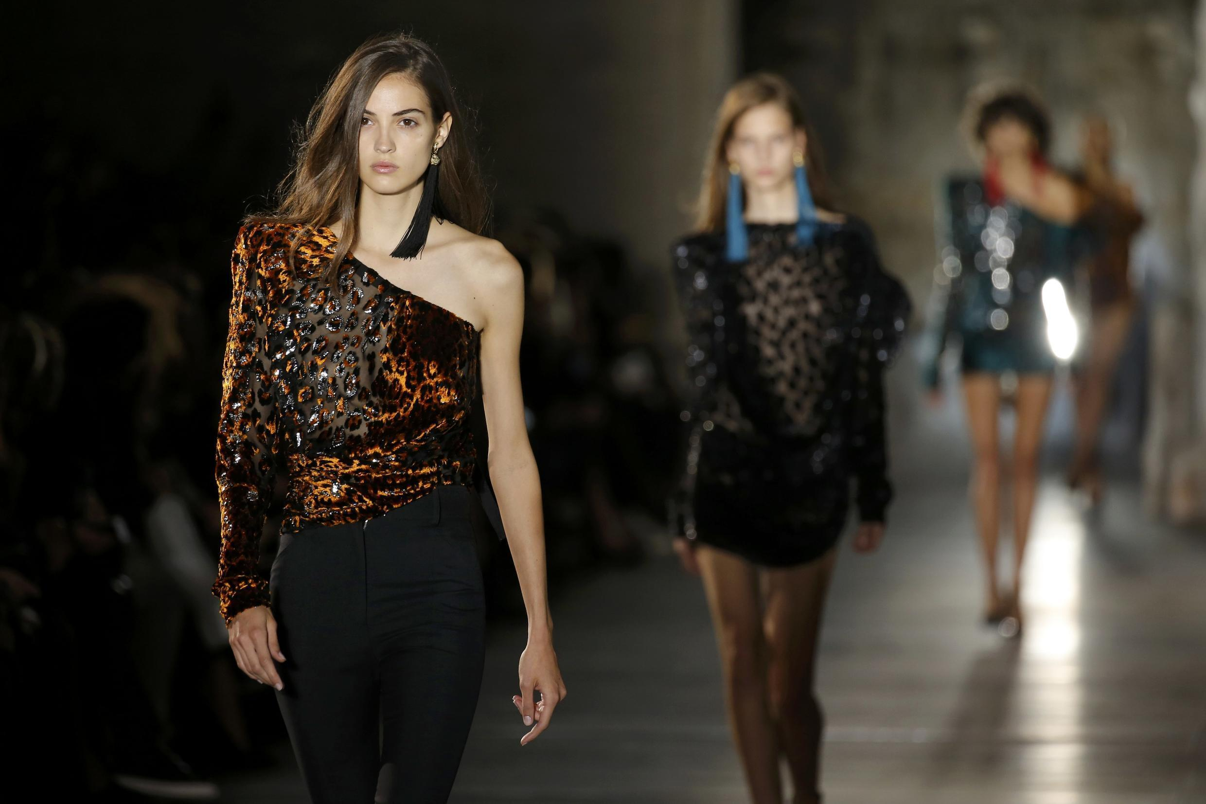 Models present creations by designer Anthony Vaccarello as part of his Spring/Summer 2017 women's ready-to-wear collection for fashion house Saint Laurent during Fashion Week in Paris, France, September 27, 2016.