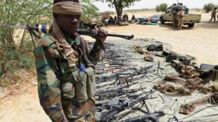 Un soldat tchadien monte la garde à côté des armes récupérées après la reconquête de Malam Fatori, le 3 avril 2015.