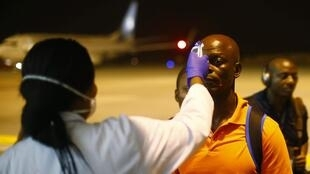 A health worker checks the temperature of a passenger at Bata Airport, Equatorial Guinea, where teams arriving for CAN must be tested for Ebola