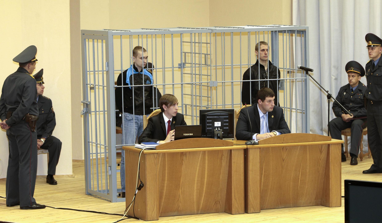 Dmitri Konovalov (G) et Vladislav Kovalev (D) dans leur cage d'accusés lors d'une comparution devant le tribunal de Minsk, le 15 septembre 2011.