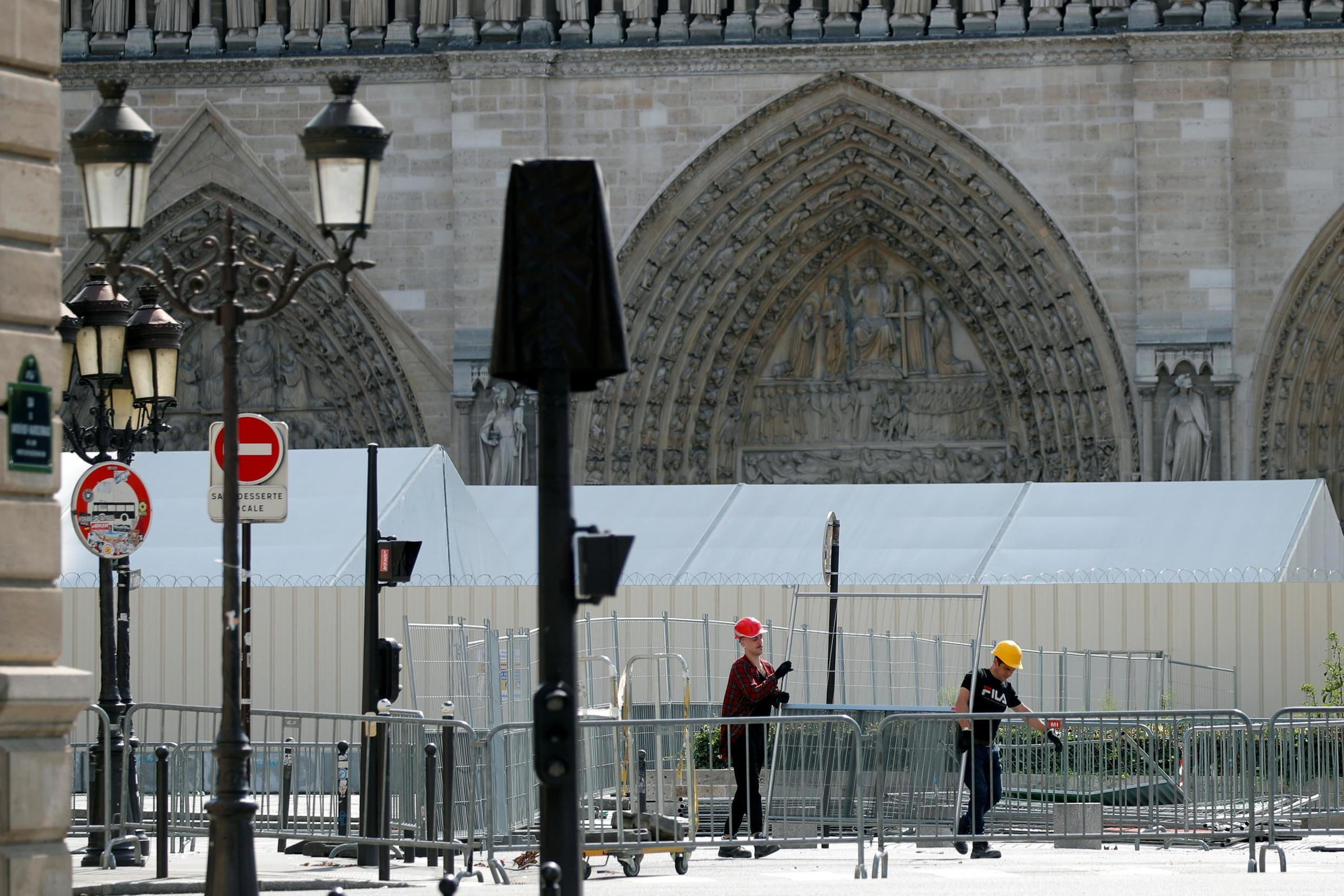 Workers install barriers around the Notre-Dame Cathedral in Paris in preparation for lead pollution clean-up operations in the surrounding streets, 13 August 2019.