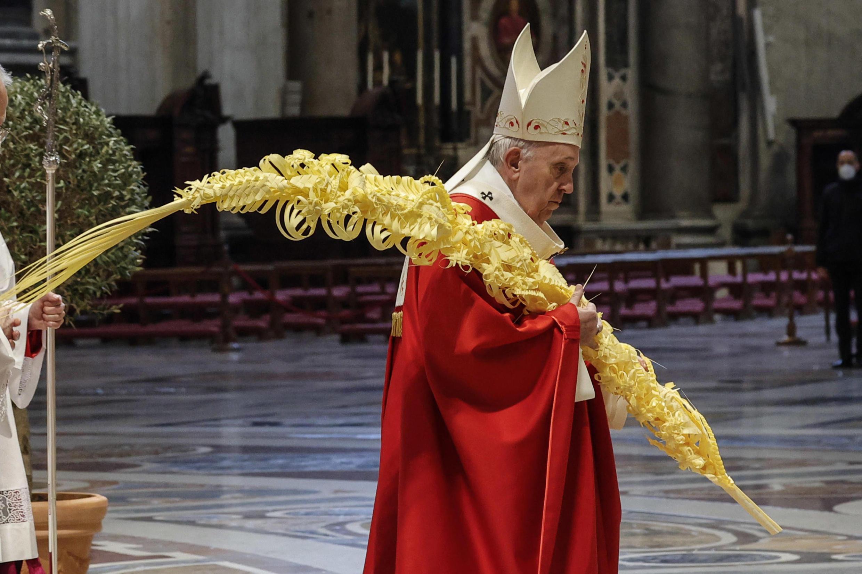 El papa Francisco sostiene una palma a su llegada a la misa del Domingo de Ramos, el 28 de marzo de 2021 en la basílica de San Pedro del Vaticano