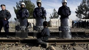 Мальчик-мигрант и полициейский кордон на греко-македонской границе, 7 декабря 2015.