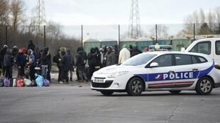 A police vehicle passes by people gathering in Calais a day after a large brawl between a hundred migrants resulted in several injuries.