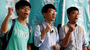 Student leaders (from L) Joshua Wong, Nathan Law and Alex Chow chant slogans before a verdict, outside a court in Hong Kong August 15, 2016.