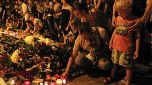 Люди приносят цветы и свечи к посольству Нидерландов в Киеве, 17 июля 2014 г.