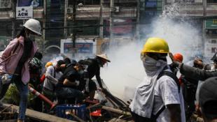 Tirs de gaz lacrymogènes lors d'une manifestation contre le putsch des militaires à Rangoun, le 2 mars 2021.