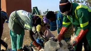 Des femmes trient et recyclent les déchets des sachets plastiques. Ici, au Burkina Faso.