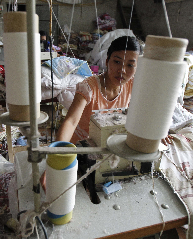Một nữ công nhân dệt may tại một xưởng may xuất khẩu, Hà Nội, 19/5/2011