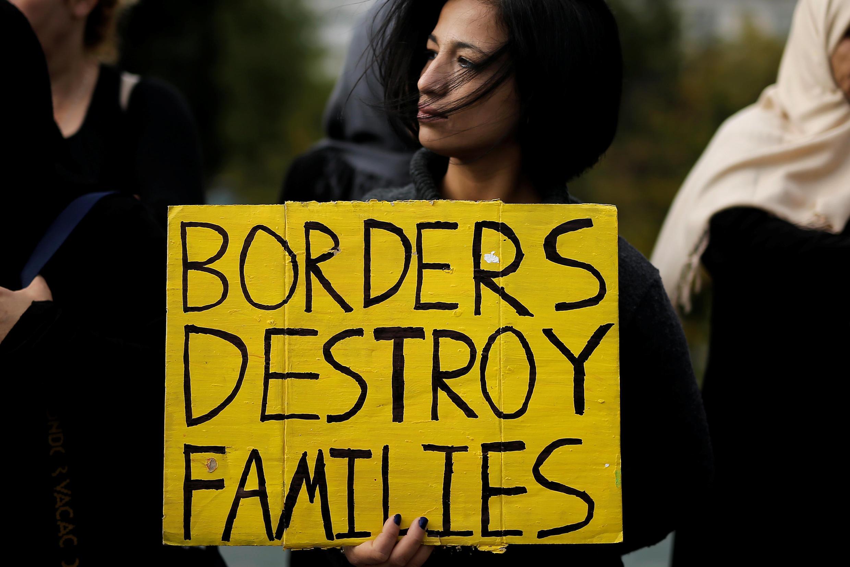 «Les frontières détruisent les familles», peut-on lire sur la pancarte de cette manifestante pour le regroupement familial des réfugiés, devant le Parlement d'Athènes, le 1er novembre 2017.