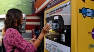 Một người sử dụng phương tiện công cộng nhét chai nước nhựa vào vào một máy thu gom để đổi lấy vé tầu..