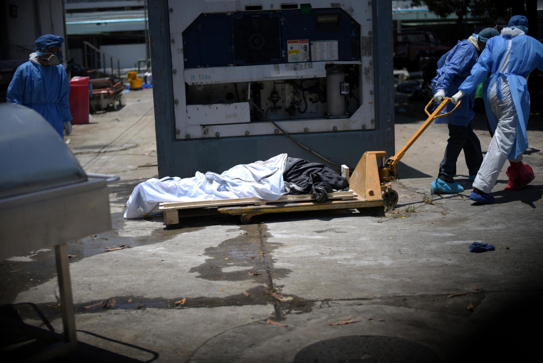 O cadáver de uma vítima da Covid-19 sendo transportado para um contêiner frigorífico, instalado do lado de fora de uma hospital de Guayaquil, no Equadro, em 3 de abril de 2020.