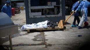 Un corps est transporté vers un conteneur frigorifique, à l'extérieur d'un hôpital de Guayaquil, le 3 avril 2020.