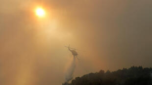 A helicopter drops water on a fire at Carros, near Nice, France in July