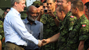 Le Premier ministre canadien Stephen Harper (G) et le président René Préval (C) saluent les militaires canadiens déployés en Haïti.