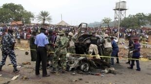 Au lendemain de l'attentat, le 2  mai, des experts dépêchés sur place examinent la voiture piégée qui a secoué la gare routière de Nyanya, à quelques kilomètres du centre d'Abuja.