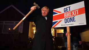 "In this file photo taken on December 11, 2019, Britain's Prime Minister and Conservative party leader Boris Johnson poses after hammering a ""Get Brexit Done"" sign into the garden of a supporter, with a sledgehammer as he campaigns with his team in London."