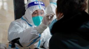 Un técnico sanitario toma una muestra de saliva a una persona para realizar una prueba de detección del coronavirus el 14 de enero de 2021 en Harbin, en la provincia de Heilongjiang, al noreste de China