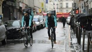 Bikers working for food delivery service Deliveroo cycle in Paris on March 31, 2017.