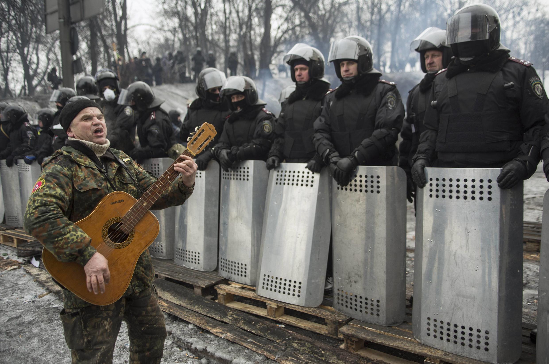 Un manifestante toca la guitarra y canta frente a los policías, en Kiev, este 28 de enero de 2014.