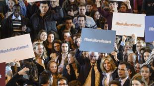 """O ministro francês da Educação, Jean-Michel Blanquer (esq.) com a esposa do presidente francês, Brigitte Macron (direita) e estudantes do ensino médio, promovem luta contra o assédio com cartaz """"Não ao assédio"""" em 5 de março , 2018."""