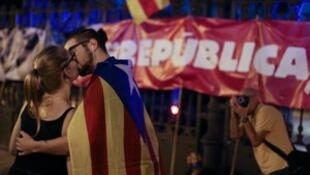 "A couple, wearing an Estelada (Catalan separatist flag), kiss next to a banner reading ""Republic"" outside Catalan Parliament in Barcelona, Spain, October 26, 2017."