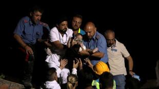 Polícia italiana e equipe médica salvam bebê depois do terremoto na Ilha de Ischia, na Itália, em 22 de agosto de 2017.