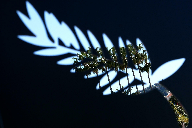 Des palmiers dans le ciel de Cannes vus à travers une ouverture sous la forme du logo de la Palme d'or du Festival de Cannes.  © Alberto PIZZOLI / AFP