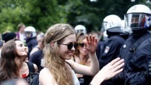 Des manifestants dansent près des policiers anti-émeutes, ce 8 juillet, au dernier jour du sommet du G20, à Hambourg.