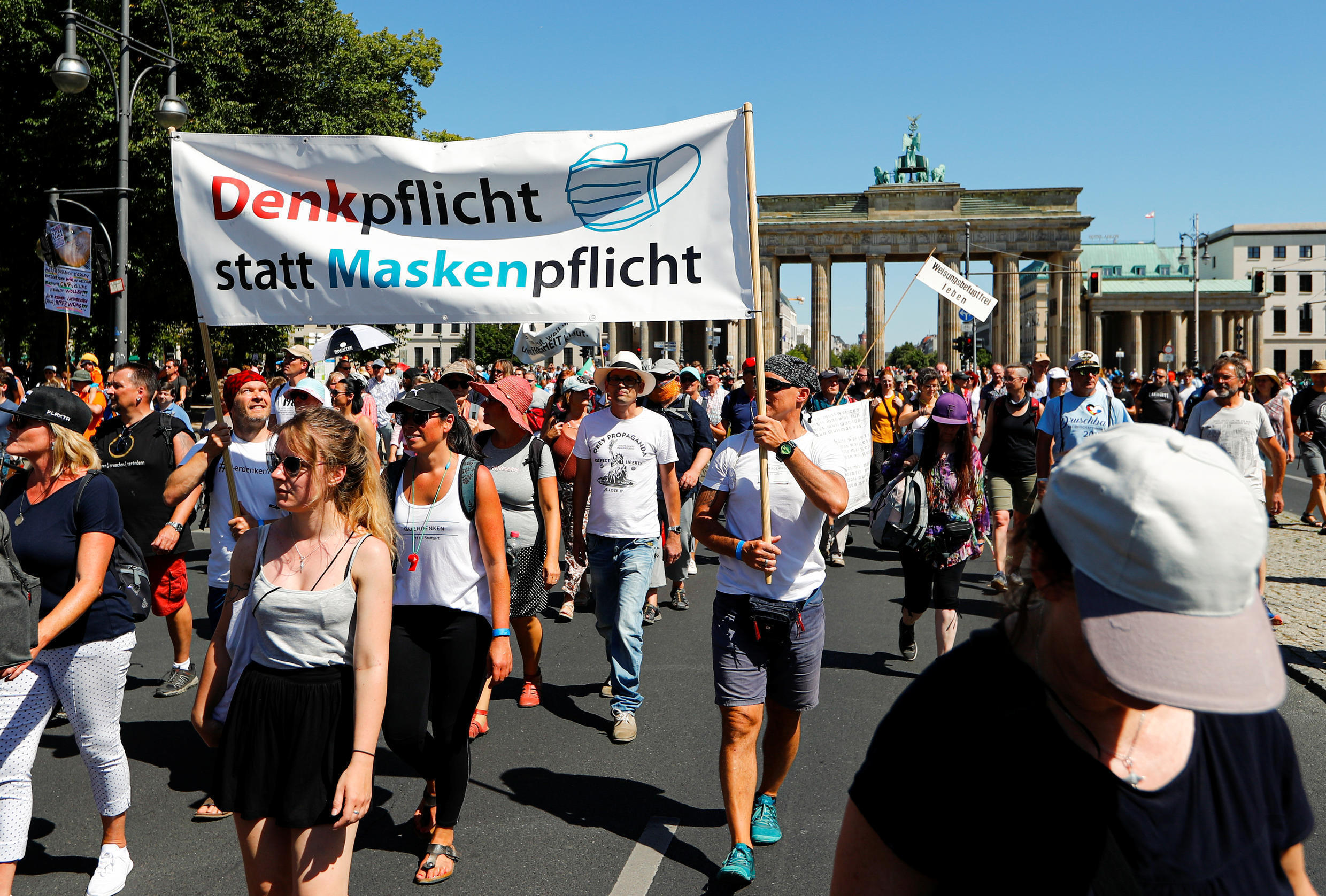 """Demonstrators hold a banner reading """"Thinking instead of masking"""" during a protest against the government's restrictions amid the coronavirus disease (COVID-19) outbreak, in Berlin, Germany, August 1, 2020."""