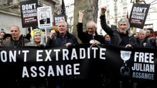 Waandamanaji wakiwa na mabango kupinga Julian Assange kupelekwa Marekani.