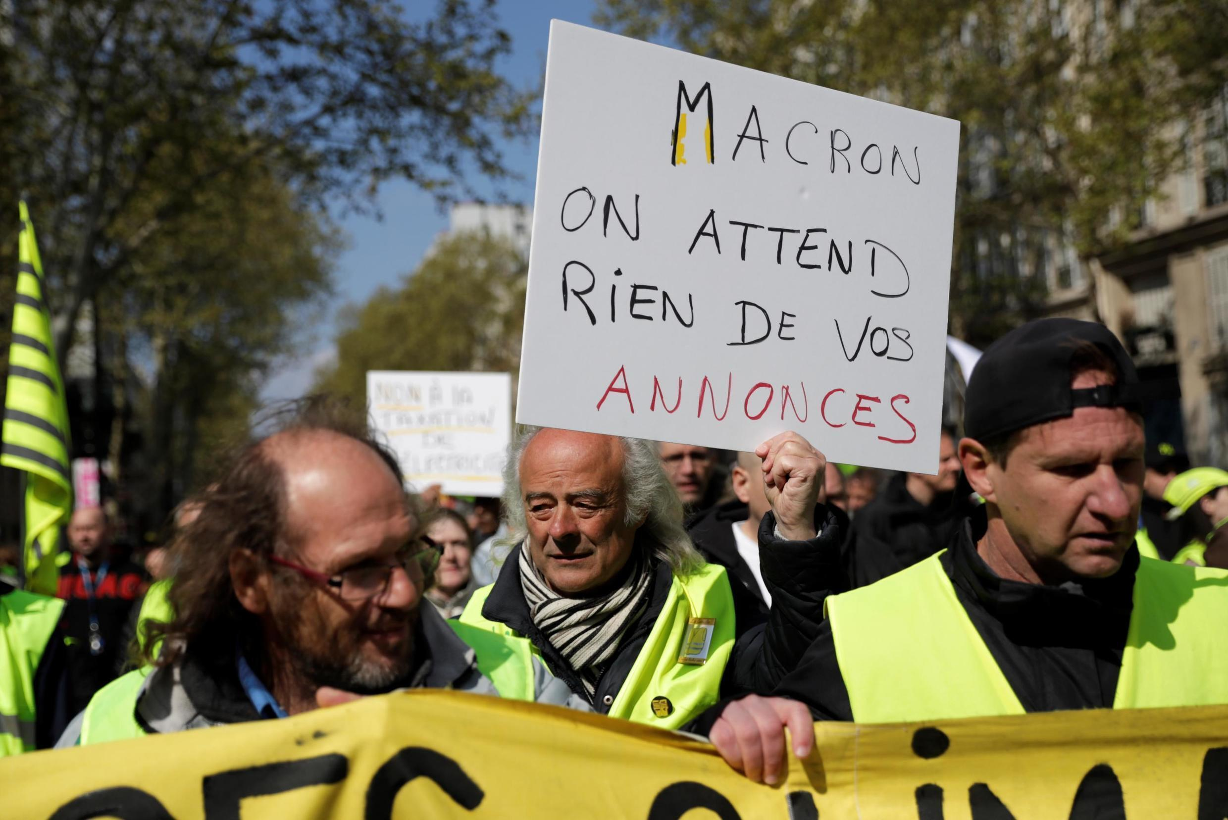 "A demonstrator holds a banner reading ""French President Macron, we don't expect anything from your announcements"" on April 13, 2019 in Paris, during a demonstration by the 'Yellow Vests' (gilets jaunes) movement on the 22nd consecutive Saturday."